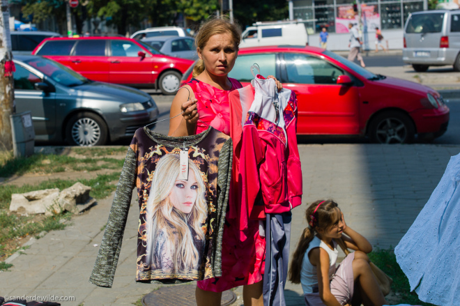 Moldova Chisinau Woman holding shirts to sell in on eo f the main streets of Chisinau