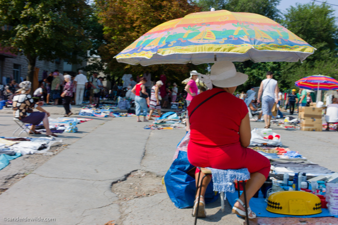 Moldova Chisinau woman in red dress under umbrella at flea market